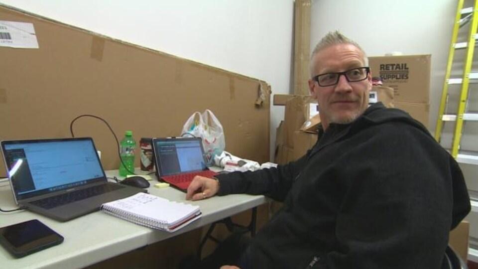 Assis à une table sur laquelle se trouvent deux ordinateurs portables et parmi des cartons vides, un homme regarde derrière lui, en biais, l'air amusé.