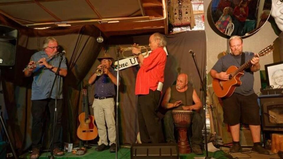 Cinq musiciens en prestation devant public.