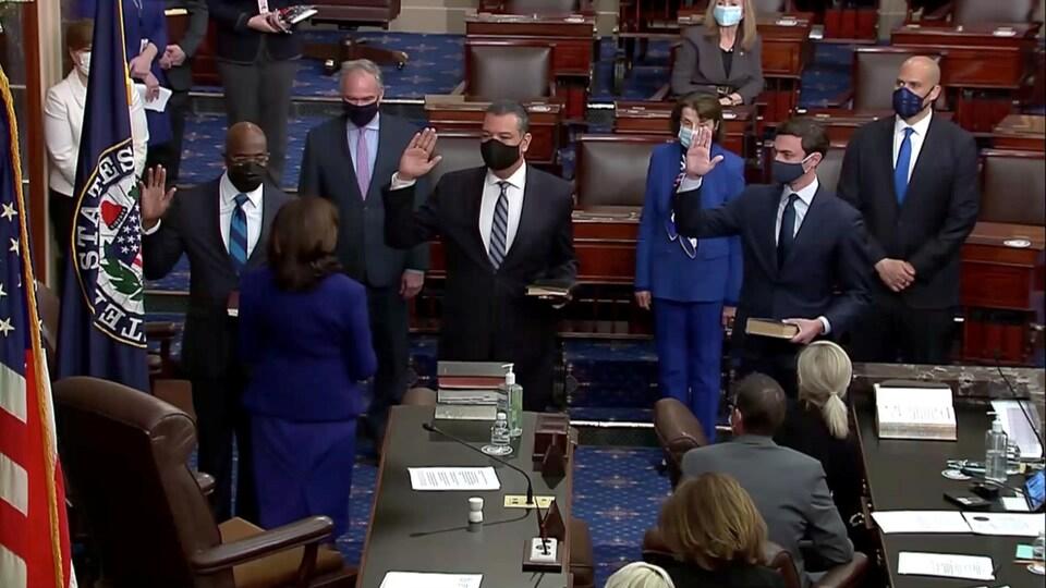 Les sénateurs Raphael Warnock (gauche), Jon Ossoff (centre) et Alex Padilla (droite) lèvent la main lors de leur prestation de serment devant la vice-présidente Kamala Harris.