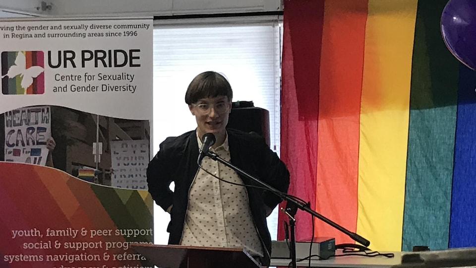 Une personne au micro avec des lunettes avec un drapeau de la fierté derrière elle.