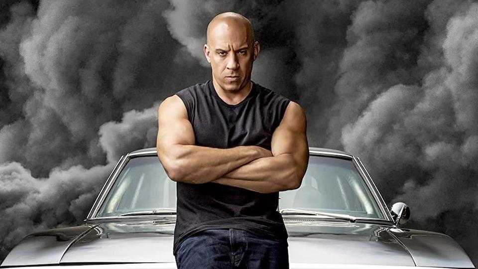 Un homme vêtu d'une camisole noire est assis, les bras croisés, sur le capot d'une voiture noire. À l'arrière, on aperçoit des nuages de fumée noire.