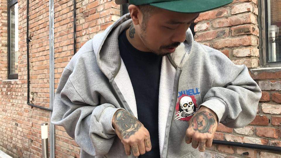 Ou Zi montre les tatouages de ses mains.