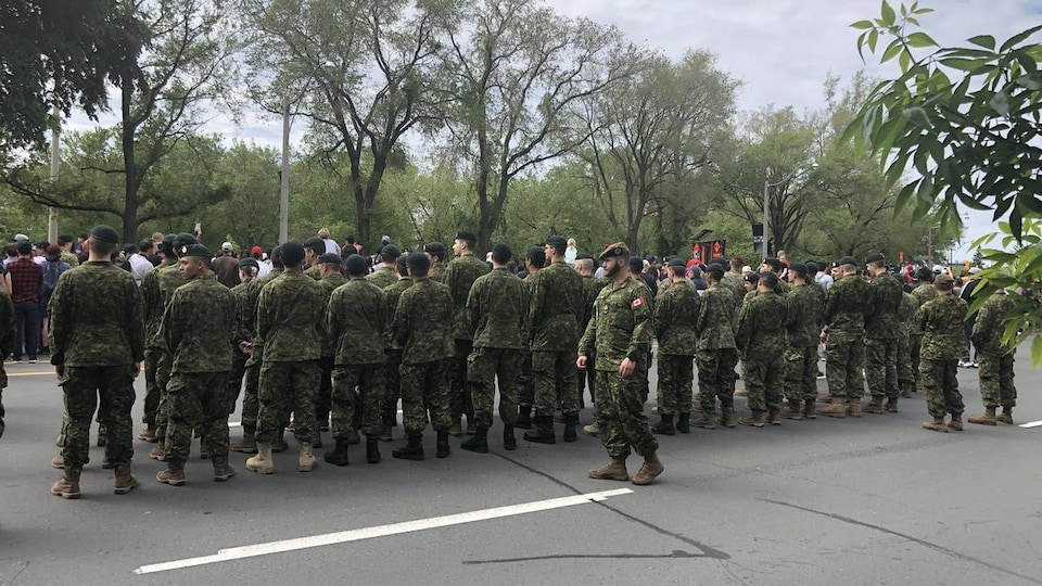 Photo d'une vingtaine des militaires en tenue qui se tiennent debout derrière un groupe des personnes.