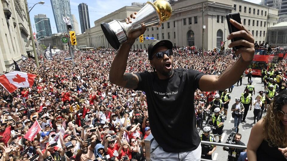Photo d'un homme tenant le trophée et se prenant en selfie.