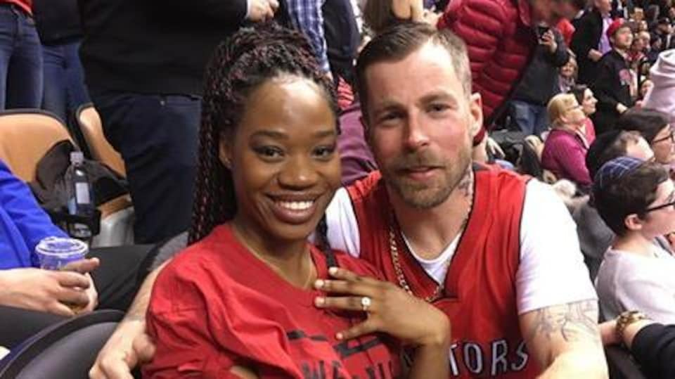 Photo d'une femme qui montre sa bague de fiançailles assise à côté d'un homme.