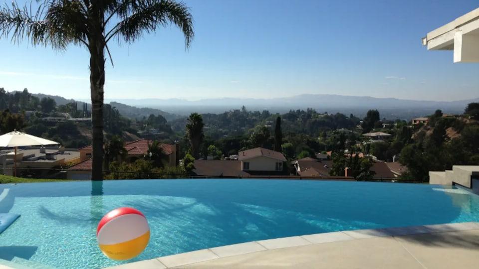 Photo d'un ballon gonflable qui flotte dans une piscine près d'un palmier.