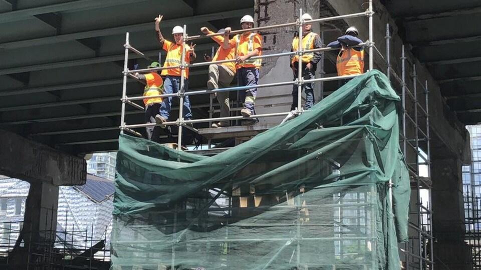 C'est sur les échafaudages que certains travailleurs des bâtiments ont pris part au défilé de Toronto à l'honneur des Raptors.