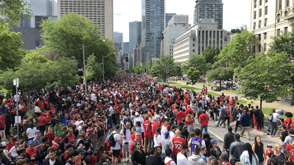 Une foule des personnes occupent une avenue.
