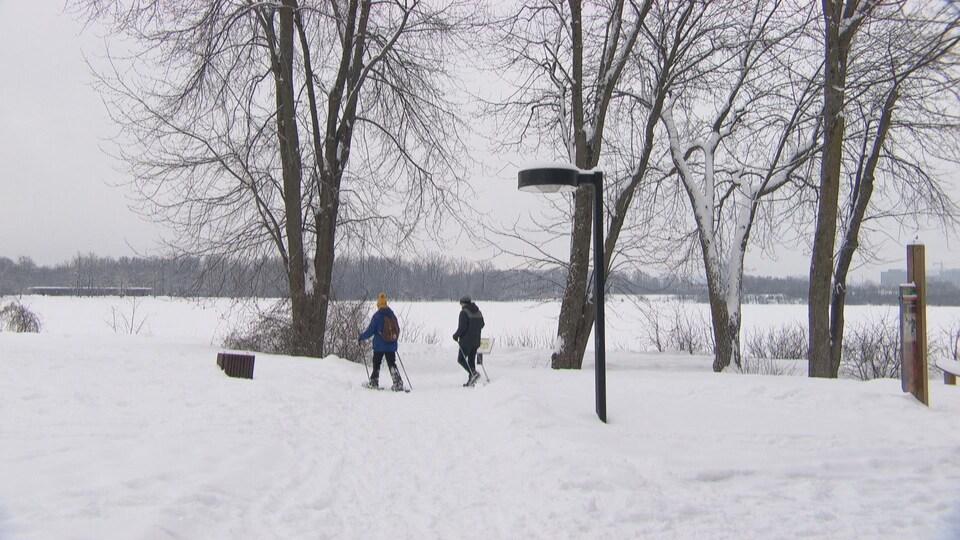 Deux personnes habillées chaudement effectuent une randonnée dans un paysage enneigé.