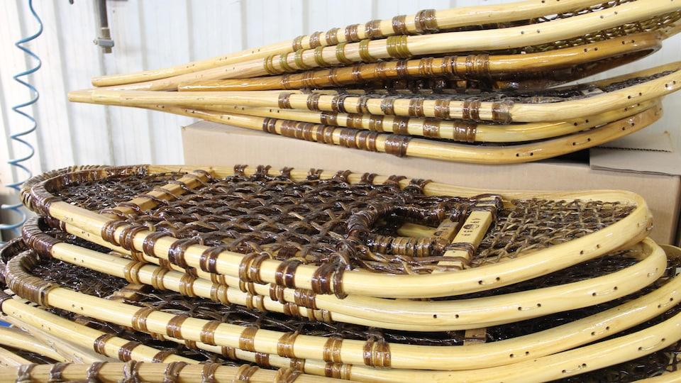 Des raquettes en bois empilées.