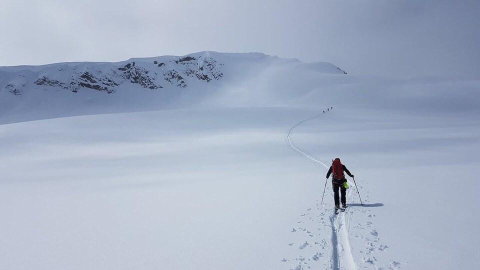 Une personne fait du ski de randonnée dans une montagne enneigée de la Colombie-Britannique.