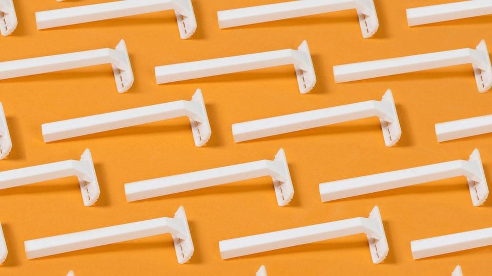 Des rasoirs blancs sur un fond orange.