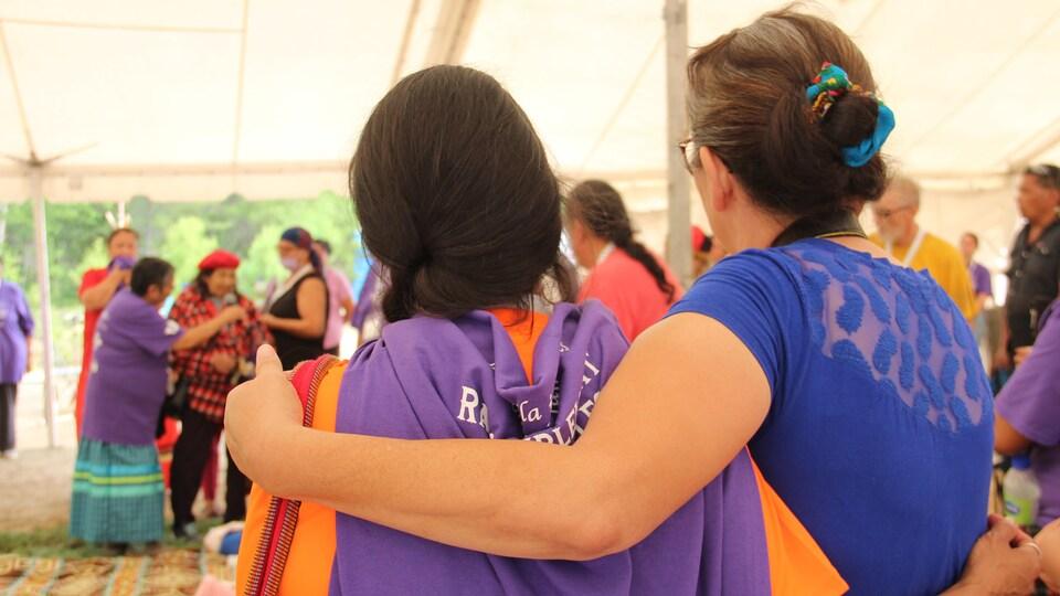 Deux femmes se tiennent bras dessus dessous.