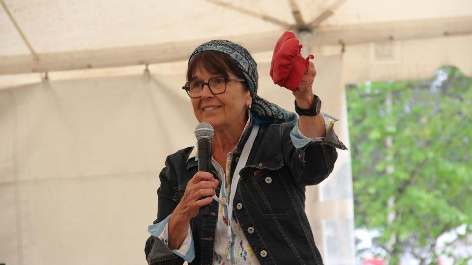 Anne Panasuk tient des mocassins d'enfant rouges.