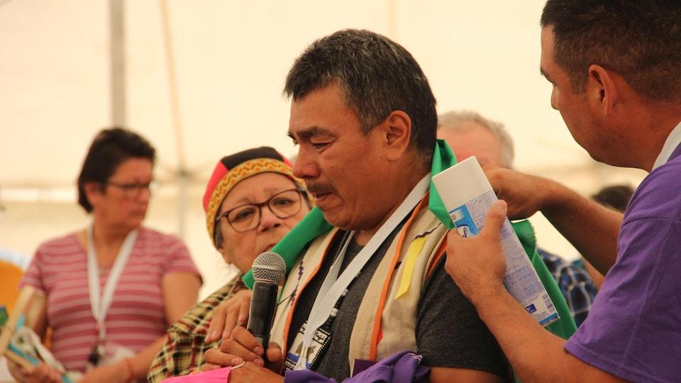 Un homme tient un micro