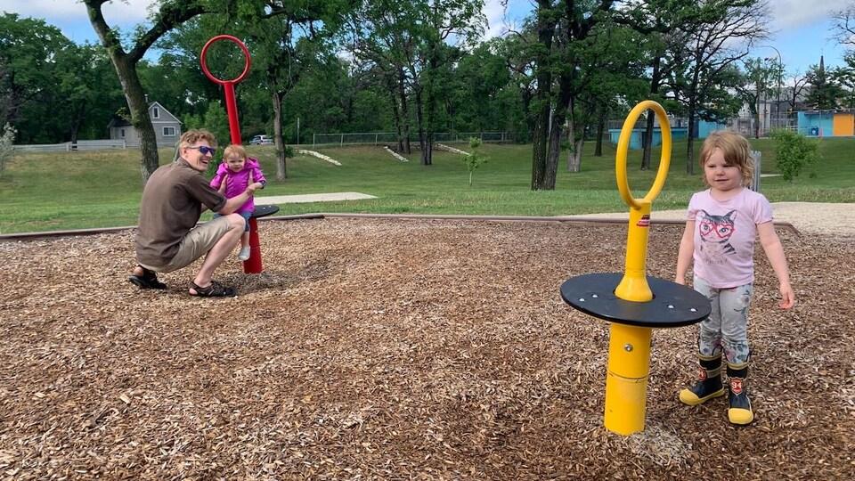 Un père joue avec ses deux filles dans un parc.