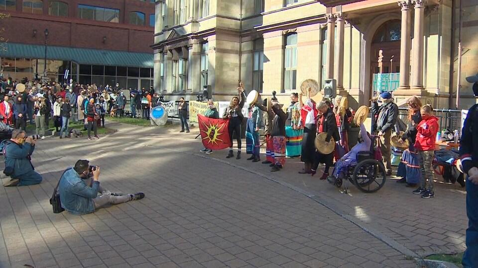Groupe de personnes rassemblées devant l'hôtel de ville pour une série d'allocutions.