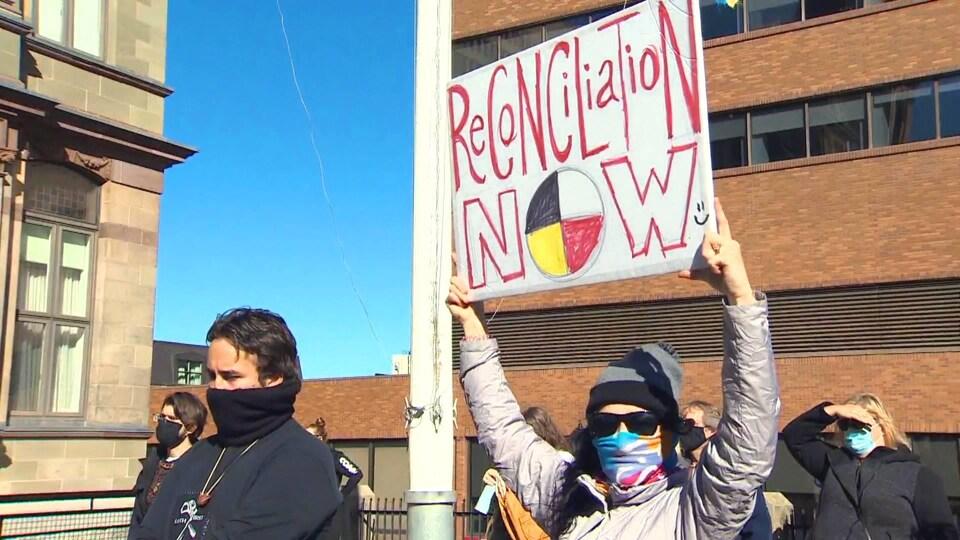 Une femme lève une pancarte sur laquelle est écrit « Reconciliation Now ».