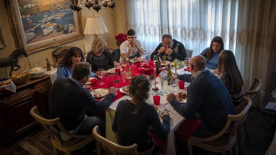 Neuf personnes mangent à une table.
