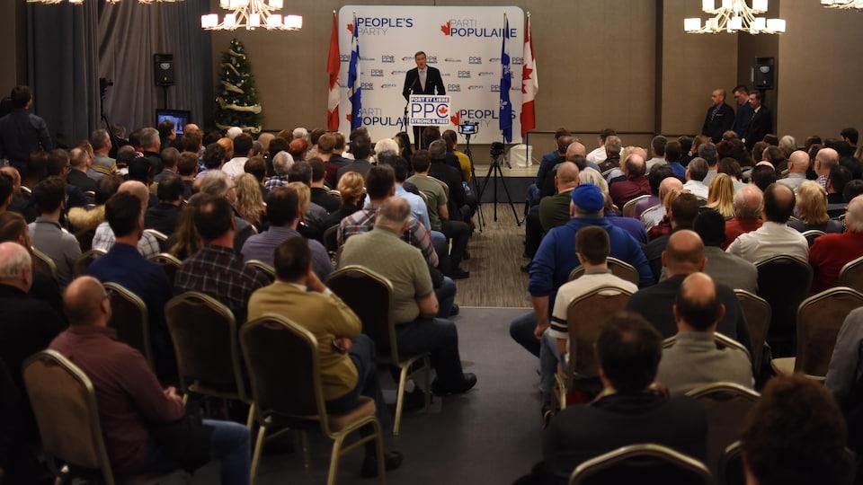 Des gens assis dans une salle écoutent un discours de Maxime Bernier.
