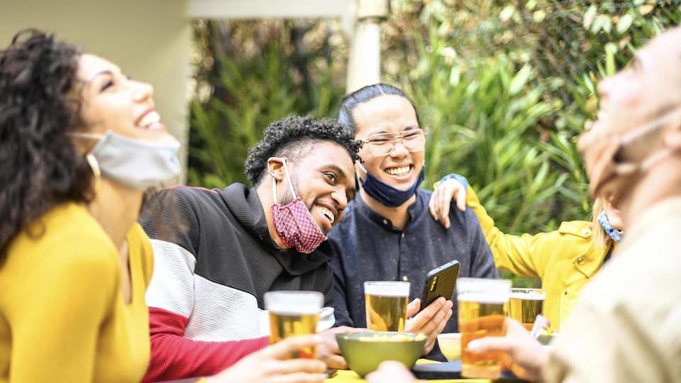 Des personnes partagent un repas autour d'une table à l'extérieur. Leur masque, accroché à leurs oreilles, est abaissé sur leur menton.