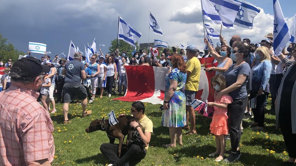 Des personnes rassemblées arborent des drapeaux israéliens.