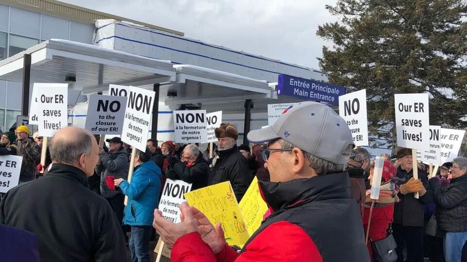 Groupe de personnes avec des affiches devant l'entrée principale d'un hôpital.