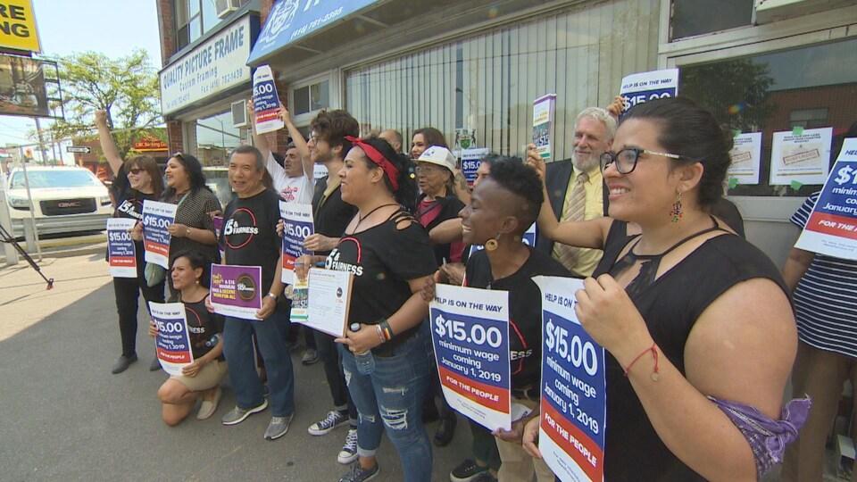 Des militants en faveur de l'augmentation du salaire minimum à 15 $ l'heure sont rassemblés dans la circonscription provinciale d'Eglinton-Lawrence, à Toronto.