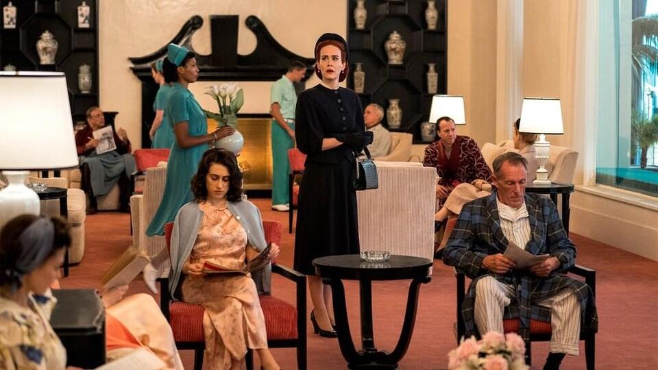 Entourée de plusieurs personnes assises, une femme habillée en noir est debout au milieu d'une pièce.