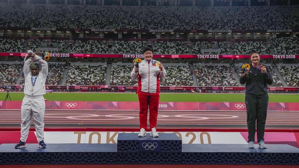 Raven Saunders, sur la seconde marche du podium, croise les bras au-dessus de sa tête alors que deux autres femmes posent pour la caméra en montrant leur médaille dans un stade.