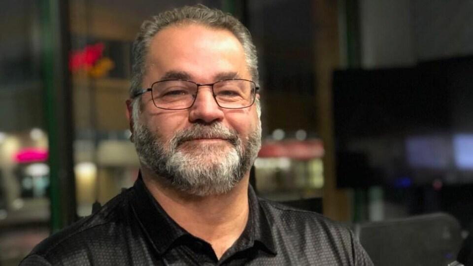 Un homme qui porte des lunettes et une chemise noire.