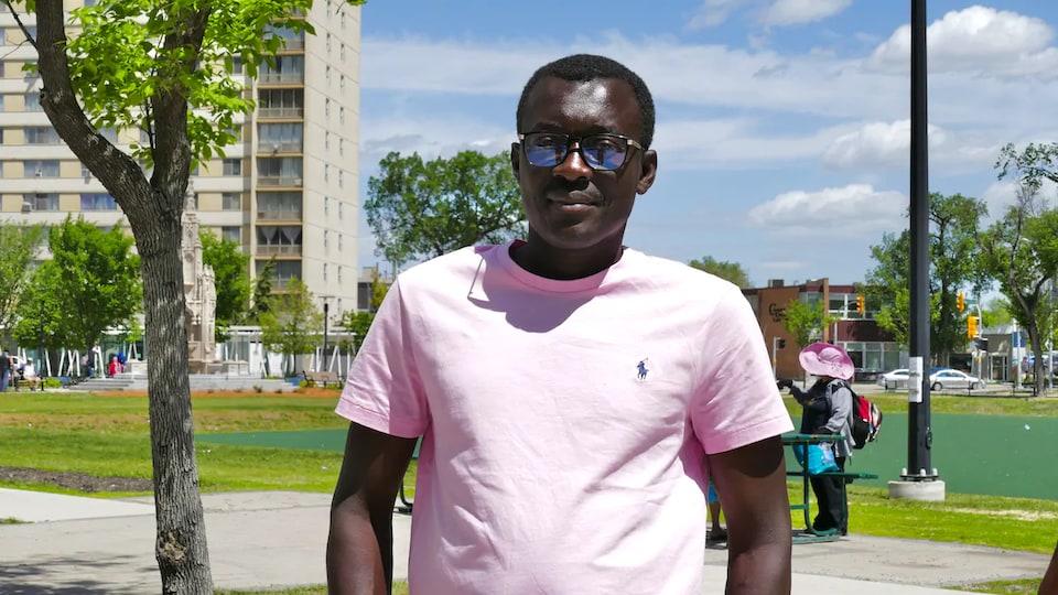 Une homme dans un parc devant un immeuble à logements.