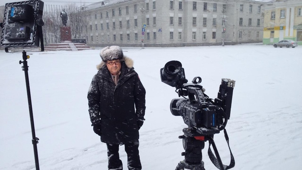 Un homme, vêtu d'un manteau et d'un chapeau recouvert de neige, se tient debout dans une cour enneigée devant une caméra de télévision et un projecteur.