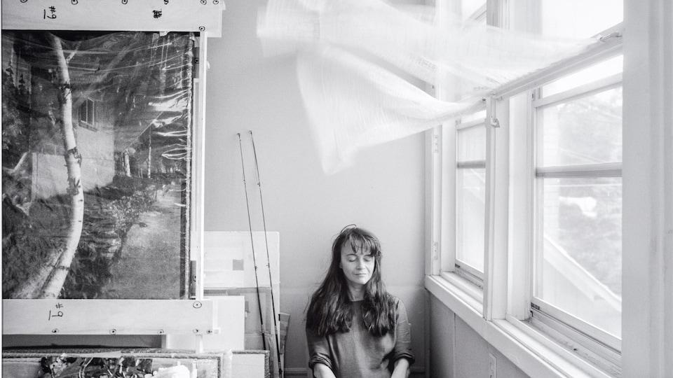 Une femme est assise devant une fenêtre à l'intérieur, un rideau est soulevé par le vent au-dessus d'elle et des tableaux sont à sa droite. La photo est en noir et blanc.