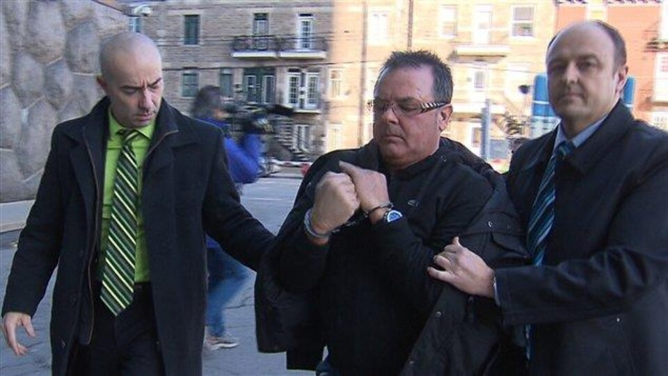 Raynald Desjardins encadré par des policiers.