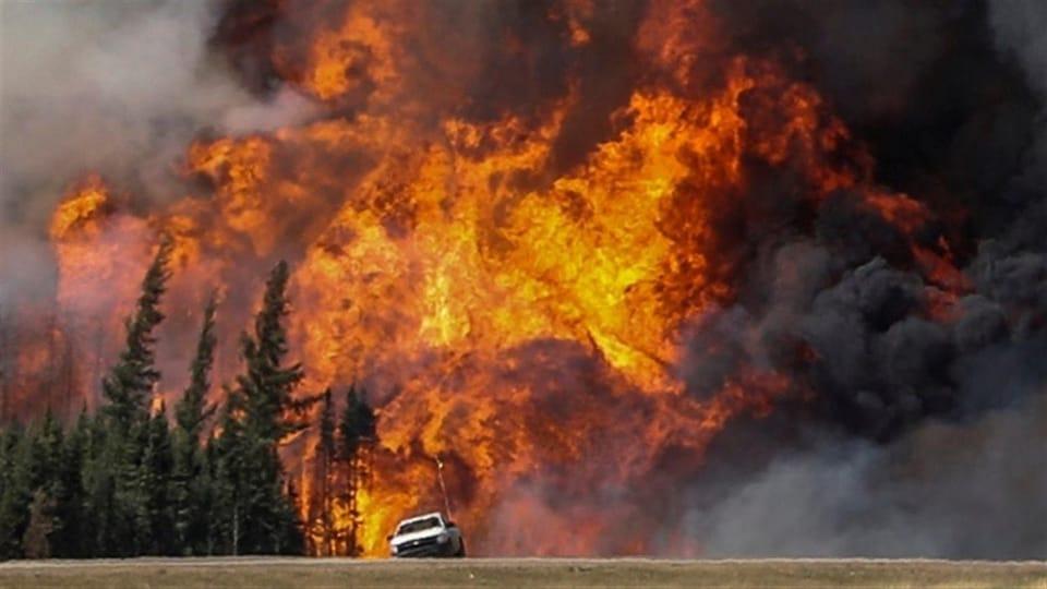 Image d'une camionnette devant un énorme feu de forêt.