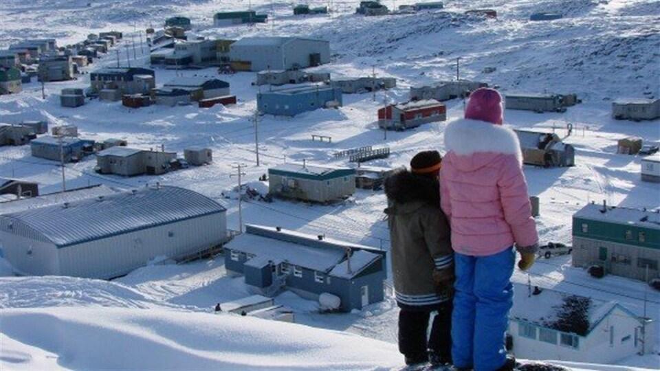 Deux enfants jettent un regard sur le village Quaqtaq, au Nunavik.
