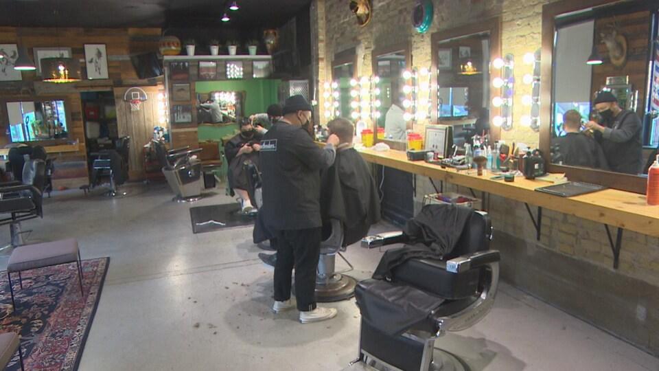 Des coiffeurs coupent les cheveux d'hommes dans un salon de coiffure à Winnipeg.