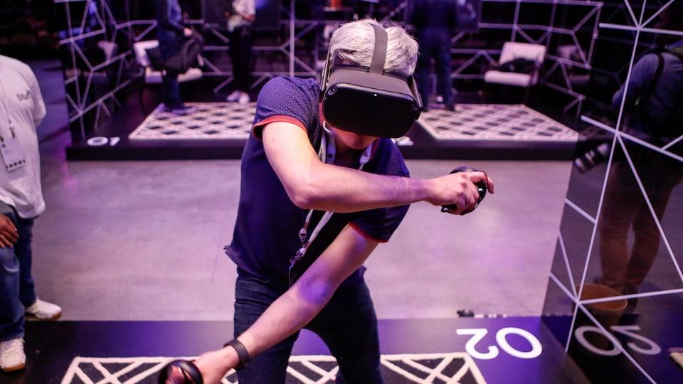 Une personne porte un casque de réalité virtuelle Oculus et tient deux manettes dans les mains. La personne est dans un centre où se tient une conférence de jeux vidéo.