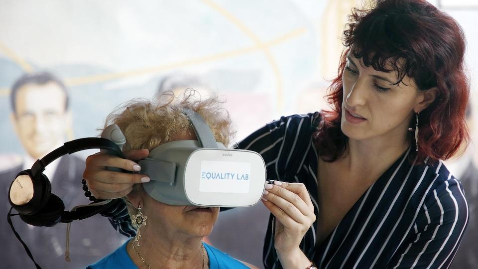 Une chercheuse ajuste le casque de réalité virtuelle sur la tête d'une personne âgée.