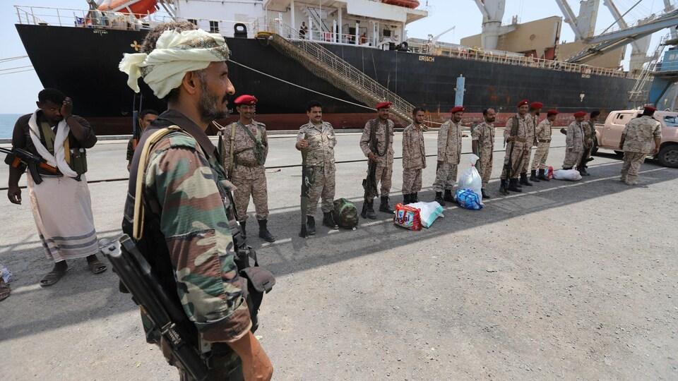 Des miliciens houthis armés se tiennent debout devant un navire au port de Saleef.