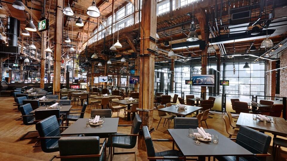 Un grand restaurant avec des poutres de bois et des murs de brique exposée.