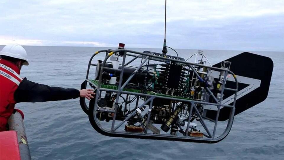 Un scientifique tient un appareil technologique en mer.