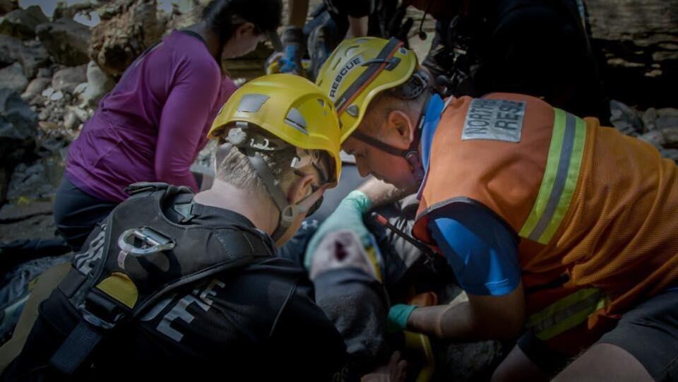 Des sauveteurs portent secours à un randonneur.