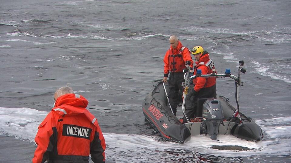 Deux hommes dans un bateau pneumatique sillonnent la rivière Mistassini.
