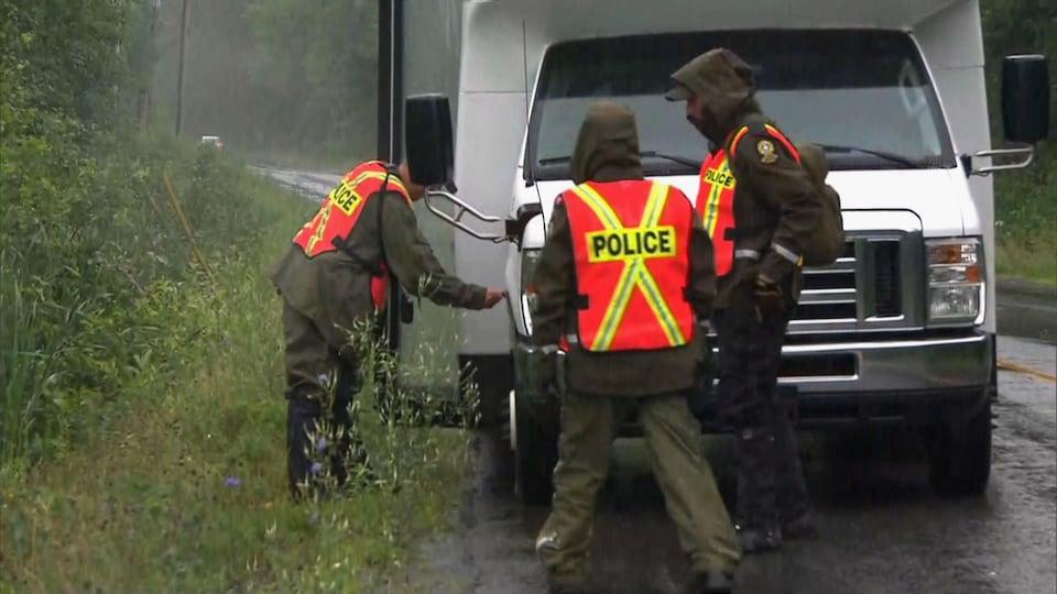 Trois policiers en habits imperméables dehors, sous la pluie, sur une route bordée d'arbres, à côté d'un petit autobus.