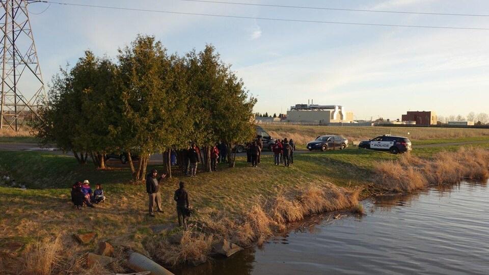 Une voiture de possible et un petit attroupement de personnes sur la berge de la rivière.