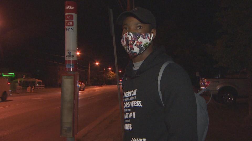 un jeune homme noir portant un masque avec des motifs, un chandail noir et une casquette noire.