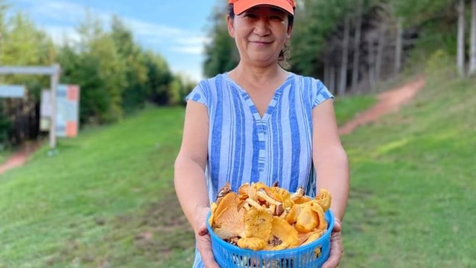 Shirley Li a un panier de champignons chanterelles dans les mains.