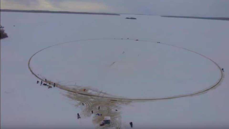 Vue de haut d'un grand cercle sur un lac glacé avec des gens autour.